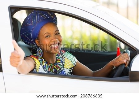 attractive south african woman giving thumb up inside her new car - stock photo
