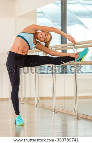 Attractive sport girl smiling and looking at camera while stretching the body in fitness class - stock photo