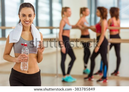 Attractive sport girl smiling, looking at camera and holding a bottle of water while standing in fitness class, in the background girls talking - stock photo