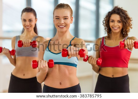 Attractive sport girls smiling and looking at camera while working out with dumbbells in fitness class - stock photo