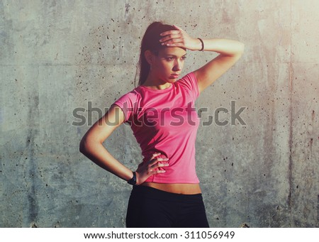 Attractive sportswomen standing on a background of gray wall after intensive fitness training - stock photo
