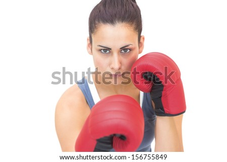 Attractive sporty brunette wearing red boxing gloves on white background