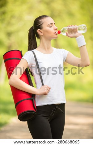 Attractive sporty girl holding mat for yoga and drinking water. Morning outdoor training. - stock photo