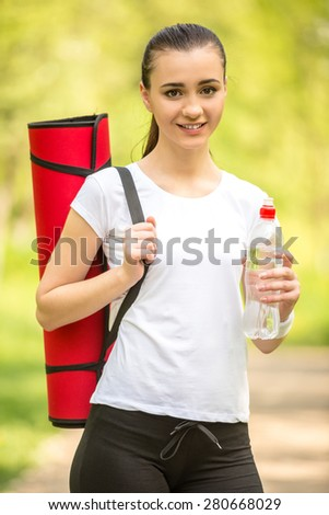 Attractive sporty girl holding mat for yoga. Morning outdoor training. - stock photo