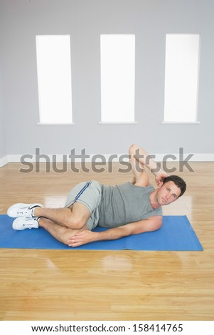 Attractive sporty man doing abdominal crunch looking at camera in bright room - stock photo