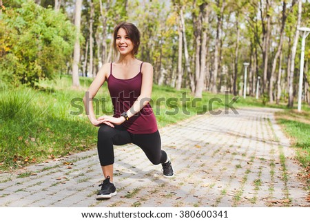 Attractive sporty smiling young woman runner stretching in park before run with smart watch cardio monitor on wrist. Performing yoga asana or lunge exercise for training calf or quadriceps. Copy space