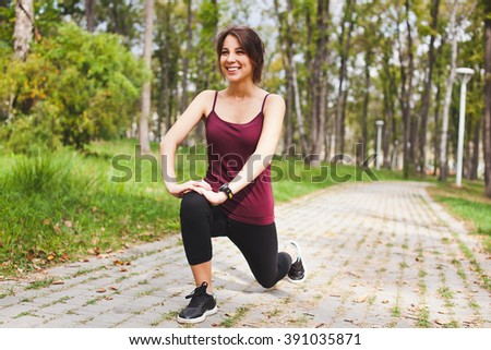 Attractive sporty smiling young woman runner stretching in park before run with smart watch cardio monitor on wrist. Performing yoga asana or lunge exercise for training calf or quadriceps. Copy space - stock photo