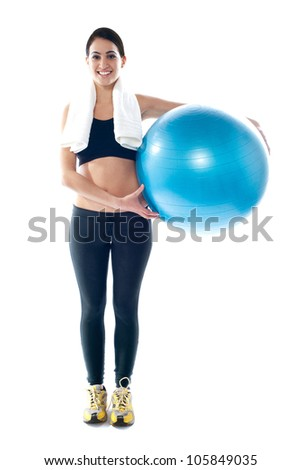 Attractive sporty teenager posing with fitness ball beside her waist - stock photo