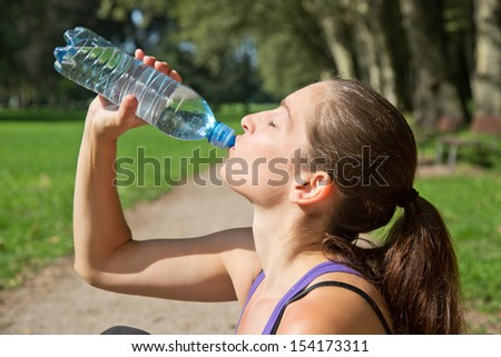 Attractive sporty woman drinking water from a bottle after jogging or running - stock photo