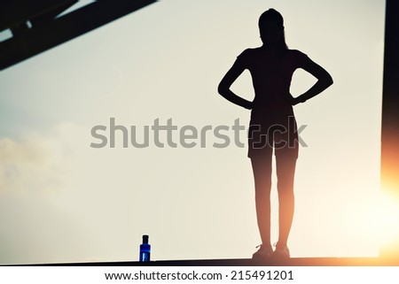 Attractive sporty women taking break after intensive evening run, woman fitness silhouette, fitness sport training in sunny sunshine, silhouette of female runner on beautiful sunset sky background - stock photo