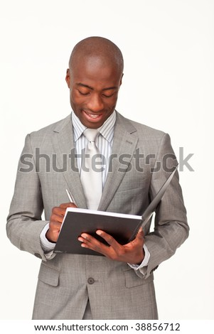 Attractive standing businessman writing notes
