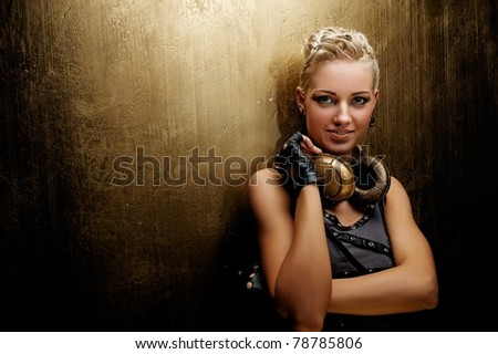 Attractive steam punk girl with headphones smiling - stock photo