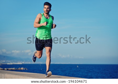 Attractive strong athlete running along the sea at evening - stock photo