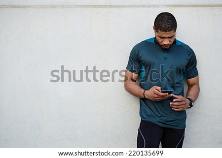 Attractive strong build runner resting after self training standing on white wall background, male runner using mobile phone, dark skinned jogger holding mobile smart phone standing outdoors - stock photo