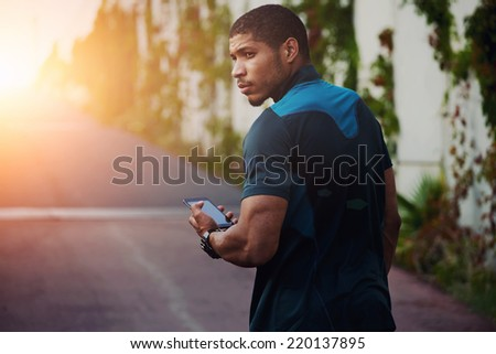 Attractive strong build runner resting after self training walking on the road, male runner using mobile phone, dark skinned jogger holding mobile smart phone walking outdoors - stock photo