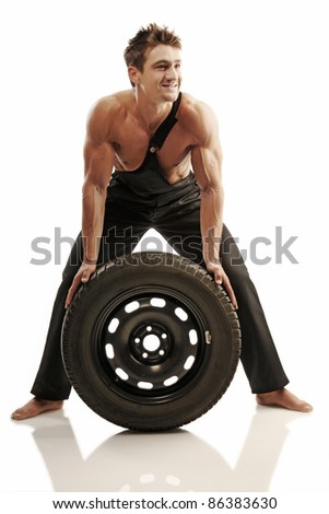 Attractive strong man with tires - stock photo