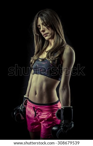 Attractive, strong woman athlete with boxing gloves