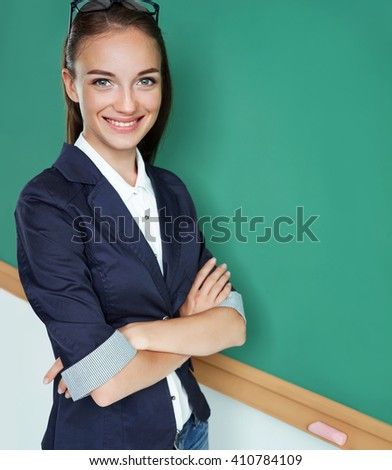Attractive student folded arms near blackboard. Photo of young student, creative concept with Back to school theme - stock photo