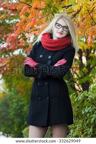 Attractive student girl with crossed arms wearing cat eye glasses is posing at red autumn foliage background - stock photo