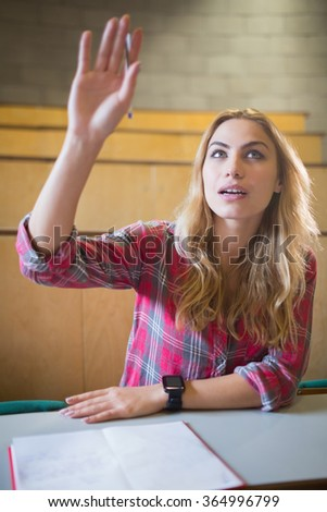 Attractive student raising hand during class at the lecture hall