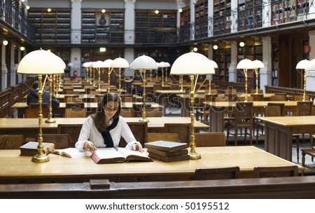 Attractive student sitting at desk in old university library studying books. - stock photo