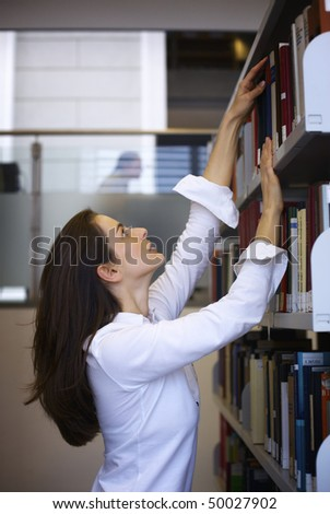 Attractive student standing in front of a bookshelf in modern university library reaching for a book. - stock photo