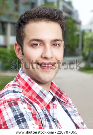 Attractive student with checked shirt laughing at camera - stock photo