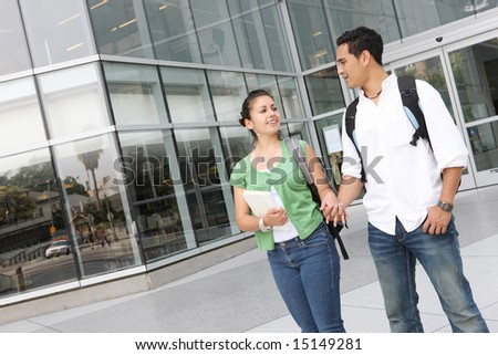 Attractive students at college reading the newspaper - stock photo