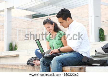 Attractive students at college studying using a laptop computer