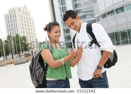 Attractive students at college texting with mobile phone - stock photo