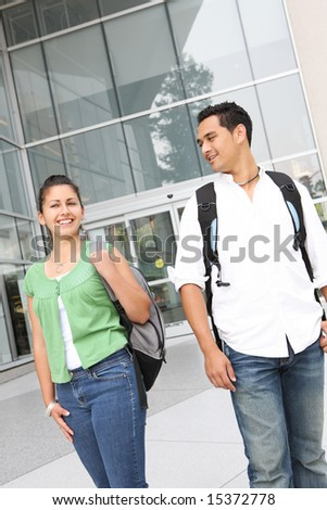Attractive students at college walking on campus - stock photo