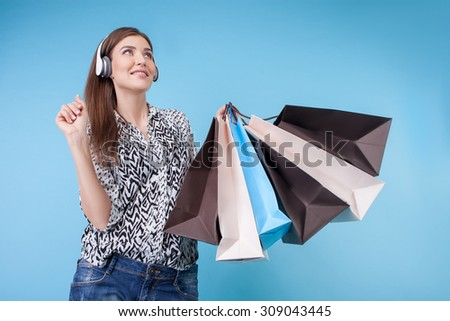 Attractive styled girl is going shopping with joy. She is listening to music from headphones and smiling. The lady is holding packets and looking up dreamingly. Isolated on blue background - stock photo