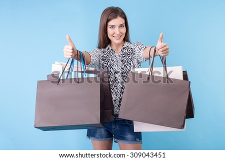 Attractive styled girl is going shopping with pleasure. She is giving thumbs up and smiling. The lady is holding packets in both her hands. Isolated on blue background - stock photo