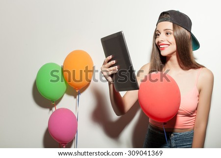 Attractive styled woman is standing near colored balloons. She is holding a tablet and looking at it with joy. The woman in cap is smiling. Isolated on background - stock photo