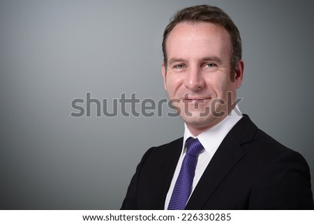 Attractive stylish businesswoman with an attentive expression looking directly at the camera, closeup of her face on a grey background with copy space - stock photo