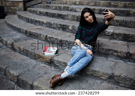 Attractive stylish hipster girl photographing herself with phone, young charming girl smiling while taking a self-ie outdoors, young tourist girl taking a self portrait with smart phone in Barcelona - stock photo