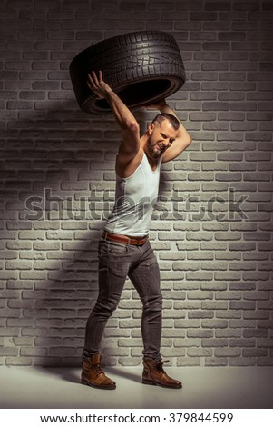 Attractive stylish man with beard holding a tire, standing against brick wall - stock photo