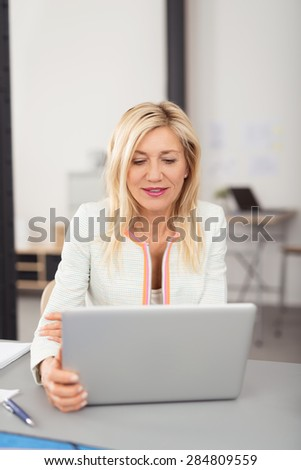Attractive stylish middle-aged blond businesswoman working on a laptop computer reading information on the screen with a serious expression - stock photo