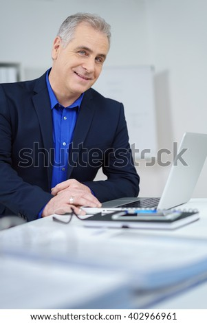Attractive stylish middle-aged businessman working at his laptop in the office pausing to look over and smile at the camera
