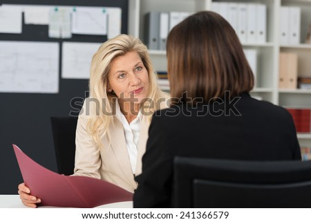 Attractive stylish middle-aged manageress conducting a job interview with a female applicant looking at her quizzically with her CV in her hand - stock photo