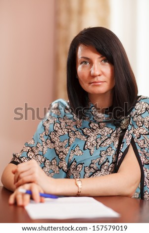 Attractive stylish middle-aged woman with long brunette hair sitting at a wooden table writing notes or a letter and looking up at the camera with a smile - stock photo