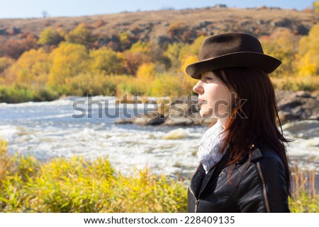 Attractive stylish woman with long brown hair wearing a trendy hat, scarf and jacket posing in countryside in front of a river, with copyspace, side view - stock photo