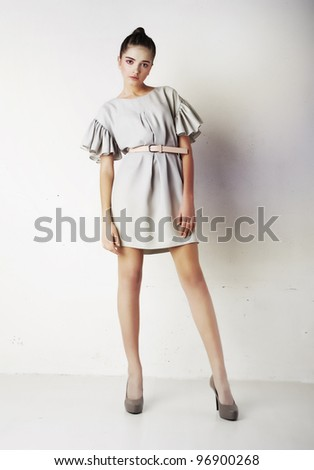 Attractive stylish young brunette female fashion model posing over white wall - stock photo