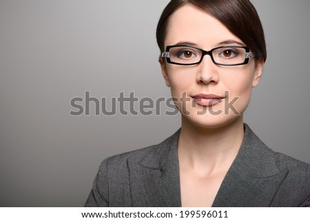 Attractive stylish young businesswoman with an attentive expression looking directly at the camera, closeup of her face on a grey background with copy space - stock photo