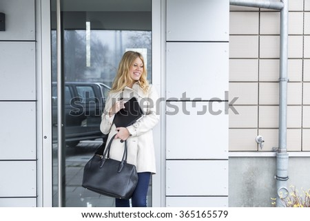 Attractive stylish young woman waiting for a business to open leaning quietly against the door with her tablet and handbag looking thoughtfully at the ground - stock photo