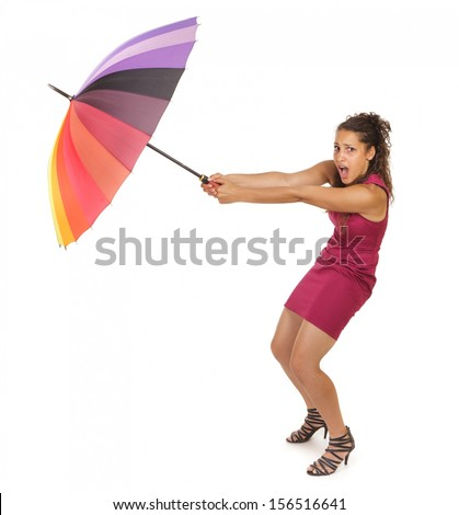 Attractive stylish young woman with curly brunette hair holding onto a colorful umbrella as a gust of wind tires to pull it from her hands during adverse weather, conceptual image, isolated on white