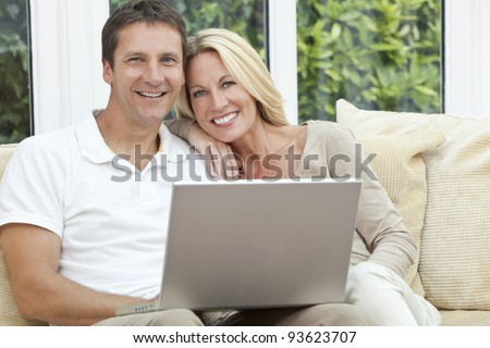 Attractive, successful and happy middle aged man and woman couple in their forties, sitting together at home on a sofa using laptop computer - stock photo