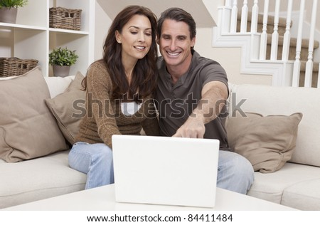 Attractive, successful and happy middle aged man and woman couple in their thirties, sitting together on sofa at home using a laptop computer. - stock photo
