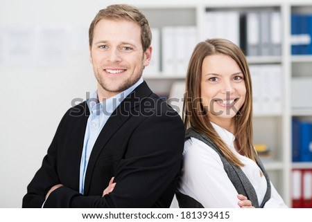 Attractive successful business partners with a young man and woman posing back to back with folded arms smiling confidently at the camera - stock photo
