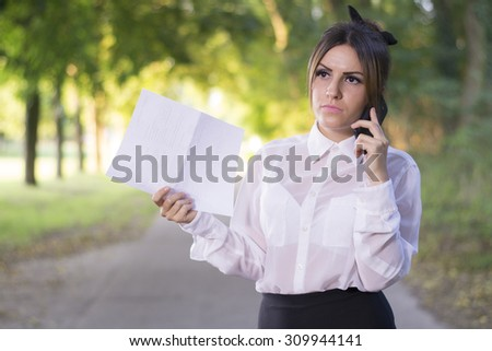 Attractive successful business woman speaks on a cell phone - stock photo